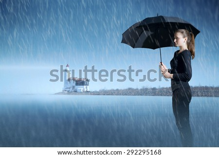 girl with an umbrella standing in the mist on the ocean at night in the rain, on the background of the lighthouse. rainy weather