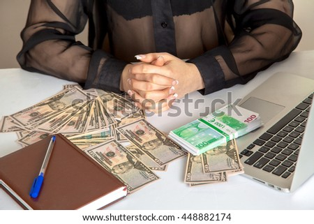 Girl with arms crossed sitting at a desk with lots of money - stock photo
