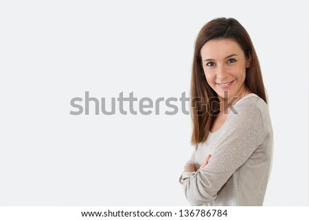 Girl with arms crossed standing on white background - stock photo
