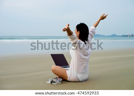 Girl with arms wide open with laptop at the beach