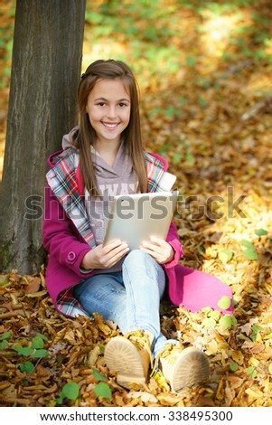 girl with autumn leaves search info for school on tablet