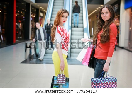 girl with bags walking with his girlfriend at the mall and shopping