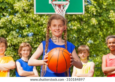Girl with ball and her team standing behind