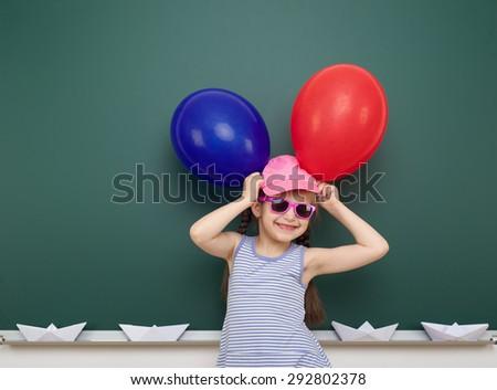 girl with balloon near the school board - stock photo