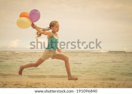 girl with balloons  jumping on the beach at blue sea shore in summer vacation in the day time - stock photo