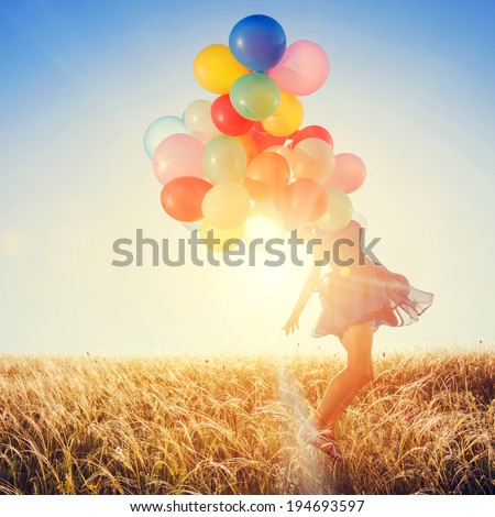 Girl with balloons running on the field to the sun at sunset.
