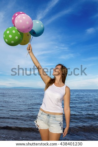 Girl with balloons with the sea background. Festive air balloons and red hair girl. Pretty woman holding air balloons. Summer holiday picture with air balloons. Colorful air balloons in front of sea - stock photo