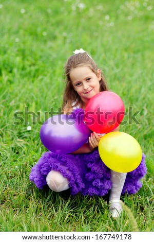 girl with balls on grass - stock photo