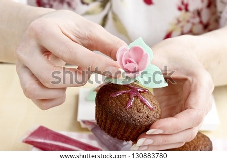 Girl with beautiful hands and nails decorating muffin - stock photo