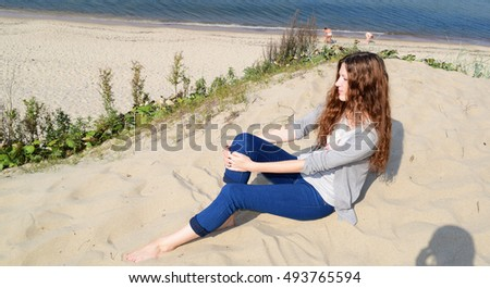 Girl with beautiful long hair sitting near the sea in nature