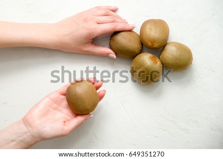 girl with beautiful nails is eating a ripe kiwi with a tea dessert spoon. Demonstration of kiwi fruit. Dark background.
