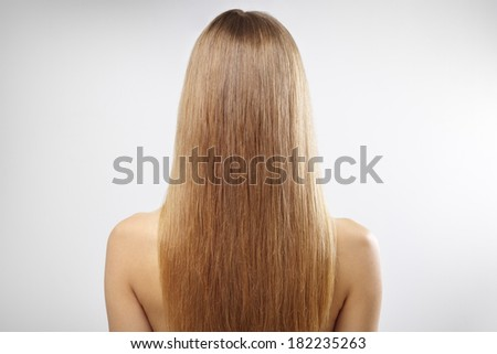 Girl with beautiful straight hair on a gray background