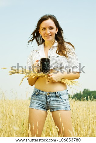 Girl  with beer and wheat ear  at cereals field - stock photo