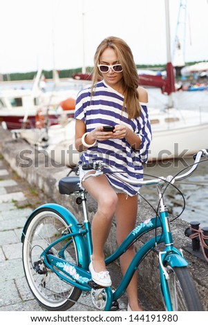 Girl with bicycle standing on the sea and yacht background. Outdoors, lifestyle - stock photo