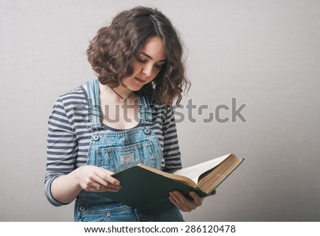 girl with big book in hand in hand on a gray background