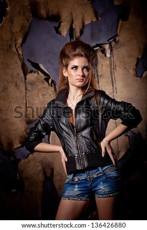 Girl with big hair posing over burned wall background, studio shot - stock photo