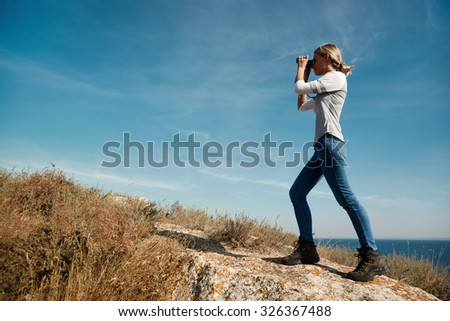 Girl with binoculars at the mountains in the rays of the evening sunset. Young beautiful woman on nature background. She is resting in the open air. Keep holding binoculars. Look ahead. - stock photo