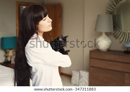 Girl with black hair style holding black cat in hands standing in bedroom interior. Relax and comfort at home