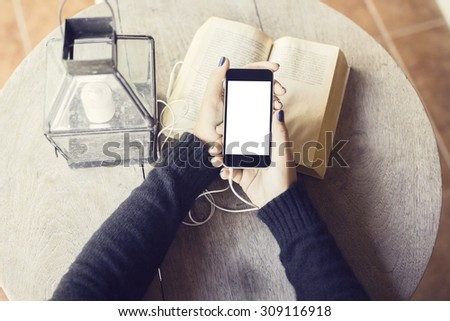 Girl with blank cell phone and books - stock photo
