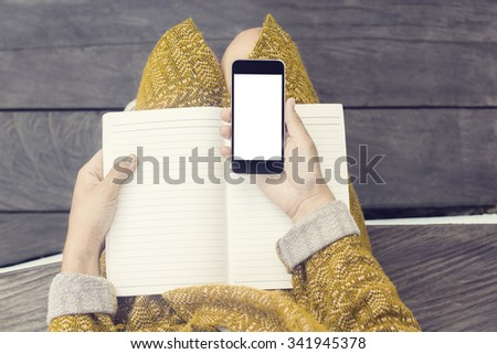 Girl with blank cell phone screen and blank diary on wooden bench, mock up - stock photo