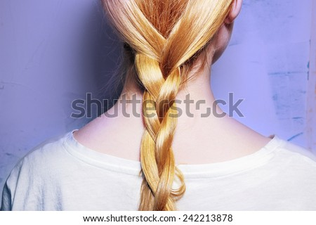 Girl with blond hair, braided into a braid on a purple background - stock photo