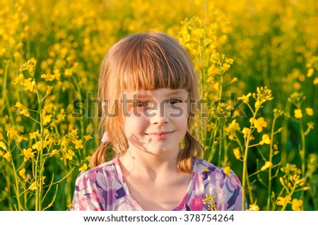 Girl with blond hair in a field of yellow flowers