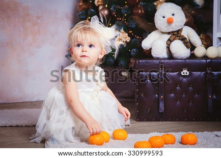 girl with blond hair sitting on the carpet. Christmas tree in the background. smiles. christmas kid under the christmas tree