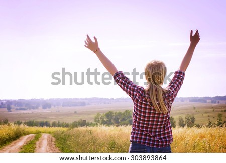 girl with blond hair standing on a rural road with his hands up. Image tinted  - stock photo
