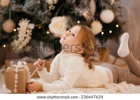 girl with blonde hair lying on the carpet. Christmas tree in the background. smiles - stock photo