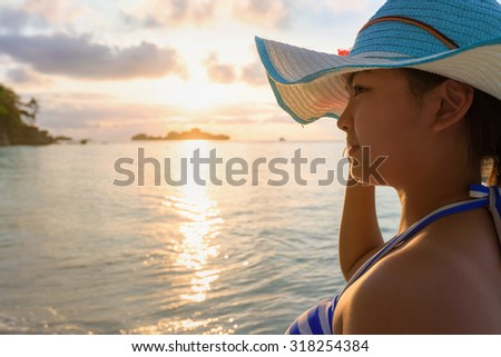 Girl with blue and white striped swimsuit standing watch nature sky and sea during the sunrise on beach of Honeymoon Bay at Koh Miang, Similan Islands National Park, Phang Nga, Thailand