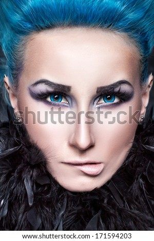 Girl with blue eyes and hair biting lips.