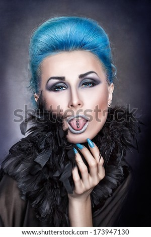 Girl with blue hair shows a pierced tongue. - stock photo
