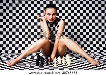 Girl with body-art thinking about progress in chess - stock photo