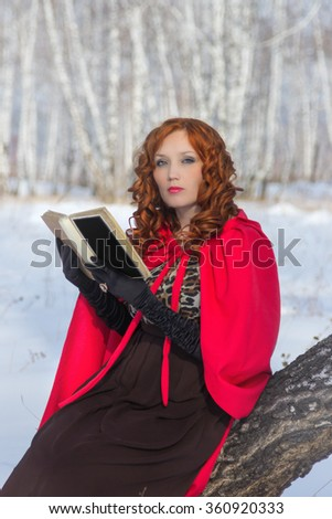 Girl with book in hand . Winter