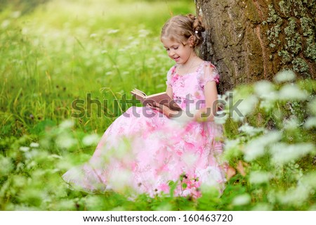 Girl with book in the park - stock photo