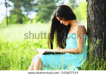 girl with book under big tree - stock photo