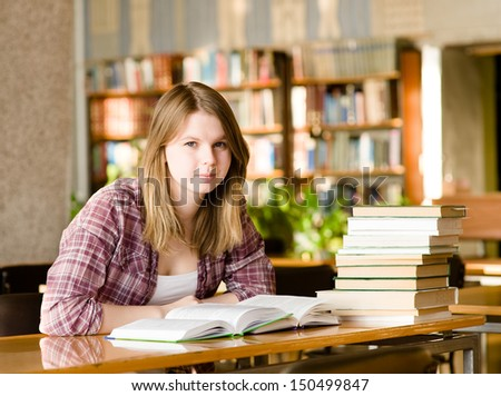 girl with books at the library. looking at camera