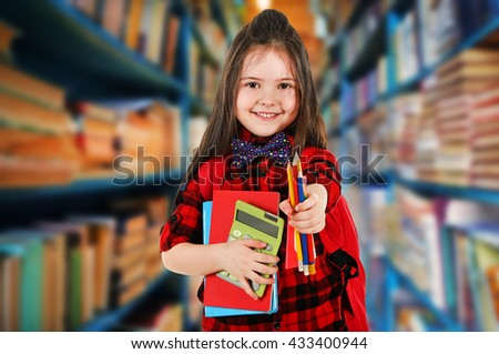 Girl with books in school library - stock photo