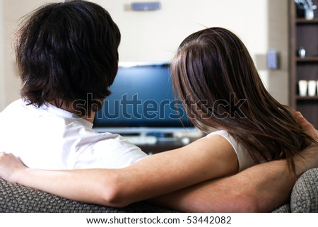Girl with boy in front of TV - stock photo