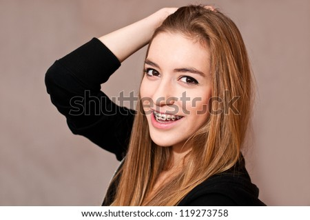 girl with braces, casual portrait, hand on her head - stock photo