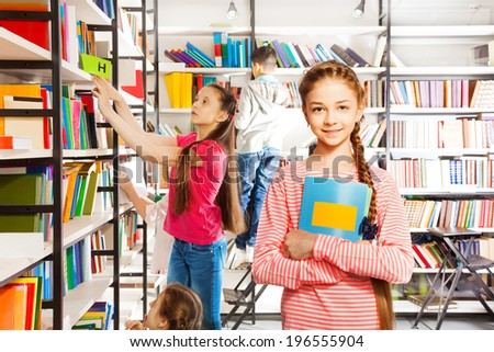 Girl with braid stands, holds notebook in library
