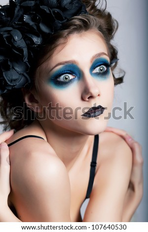 Girl with bright unusual conceptual make-up (painted face) closeup portrait