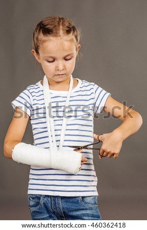 Girl with broken arm is standing on the gray background  and trying to cut her gypsum.