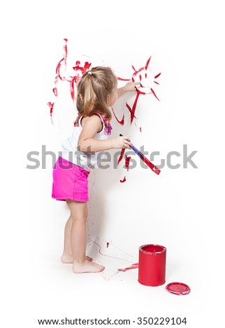 Girl with brush in hand finger paints merry sun on a white wall - stock photo