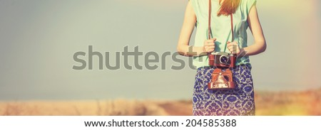 girl with camera on country side - stock photo