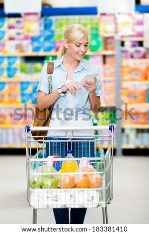Girl with cart full of food in the market. Concept of consumerism, retail and purchase