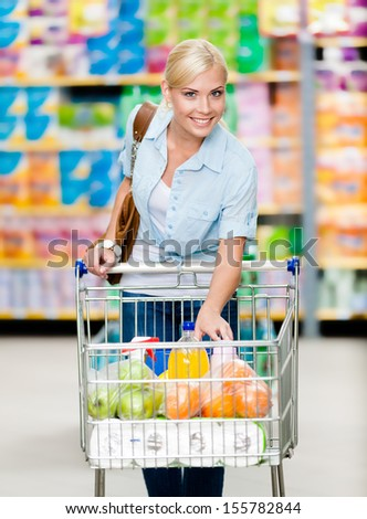 Girl with cart full of food in the shopping center. Concept of consumerism, retail and purchase - stock photo