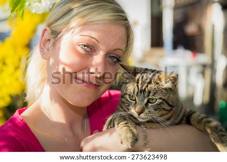 Girl with cat in the garden - stock photo