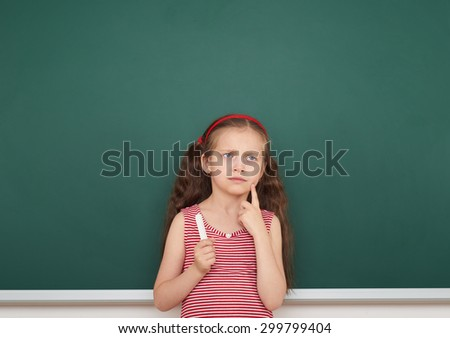 girl with chalk write on school board - stock photo