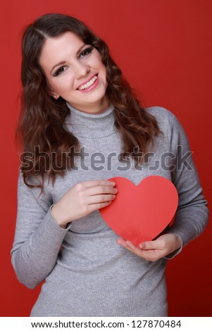 Girl with charming smile holding red heart symbol on Valentine Day - stock photo